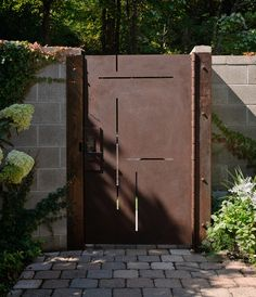 A Cor-Ten steel gate with Mondrian-style laser cuts creates visual interest as well as purpose. The lines were carefully placed at the clients' (and their dog's) eye levels so everyone can see who's at the door before opening it.