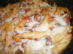 Italian Sausage and Penne Bake: 3 links mild Italian sausage, 2 garlic cloves minced, 1 tablespoon olive oil, 1 tbsp tomato paste, 1 tbsp balsamic vinegar,  2 (15 ounce) cans diced tomatoes, salt to taste, oregano to taste, ground red pepper, 8 oz. penne pasta - cooked, 1 cup shredded Italian cheese blend.