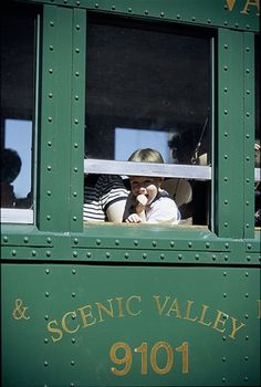 the BOONE AND SCENIC VALLEY RAILROAD'S diesel locomotive pulls passengers—in an open-air railcar or caboose—across a 156-foot-high trestle bridge above the river valley near Boone.