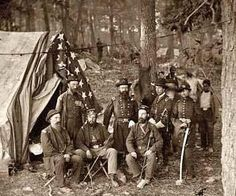 Antietam, Maryland. General John C. Caldwell and staff on battlefield. It was taken in 1862 by Gardner, Alexander, 1821-1882.    The image shows United States trrops. A US Battle Flag is seen behind the men.