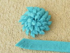 Fun felt flower tutorial: felt folded in half, cut along the full length on the diagonal and then rolled up and glued together. Sounds pretty simple and looks great!