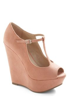 Crafted from luxe, vegan faux suede and reaching heights of almost six inches, these tall platforms feature a T-strap and peep toe, all in a girly-glam shade and shape you adore.