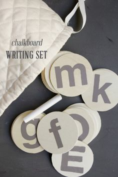 """Chalkboard paint (2 coats) or chalfboard contact paper on wooden discs. Needs to be """"seasoned"""" by rubbing chalk all over, then erasing before first use. Kept with a letter formation chart."""