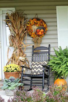 Fall porch decor with cornstalks, DIY wreath, and chevron pillows