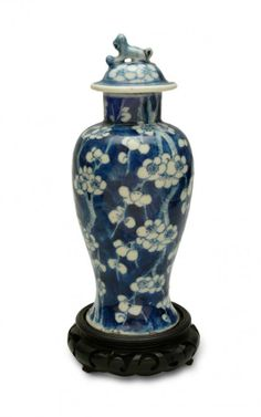 Vase with cover, China, Qing Dynasty, Kangxi mark porcelain, underglaze blue paints; decorated with blossoming plum tree, wooden, carved stand; height 22 cm