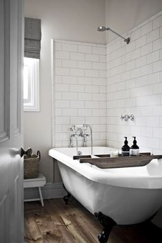 subway tile bathroom and those rustic wood floors with that claw foot tub.