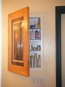 Bathroom cabinet concealed behind picture frame door.