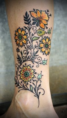 Colorful flower design tattoo on legs