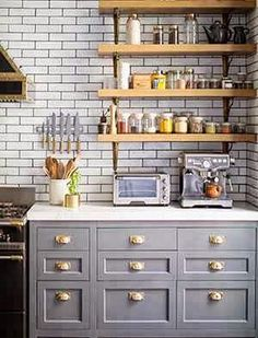 Kitchen in a New York apartment with grey cabinets with brass pulls, wall mounted shelves, marble countertops and subway tile walls on dark ...