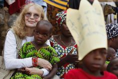UNICEF Goodwill Ambassador Mia Farrow holds a small child while watching a dance performance at a transit and orientation centre for girls who have survived sexual violence and other abuse in Bukavu, Democratic Republic of the Congo. The UNICEF-supported centre, run by the Congolese NGO BVES, provides shelter, health and psychosocial services, and education and vocational skills training. Children of the girls are also supported.   © UNICEF/Olivier Asselin   http://www.unicef.org