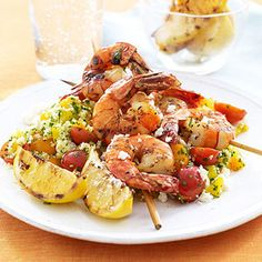Greek-inspired shrimp skewers over couscous tossed with bell peppers, tomatoes, and chopped parsley.