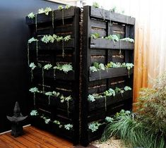 This vertical planter was built as a functional screen to hide an unsightly water tank from a kitchen window. A low-maintenance succulent pallet garden is a clever solution!