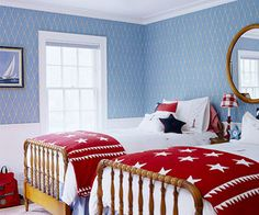 Nautical flair mixes with American pride in this children's bedroom. Instead of using intense flag colors on the walls, light blue wallpaper and white wainscoting keep the light-filled room airy. Bright red and deep navy accents (pillows, lamp, quilts) stay true to Old Glory's colors. Stars add a fun touch to the room.