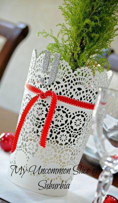 Lacey containers filled with mini green tree's, a red ribbon and sparkle letters that spell JOY. Very simple and beautiful. Dinning Room Christmas house tour My Uncommon Slice of Subrubia