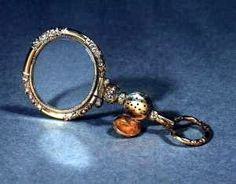 The quizzing glass was popular with both men and women from the 18th Century onwards. The gold handle of the example shown revolves and features a central compartment for containing a vinaigrette. Quizzers have also been made combined with watch keys or compartments to keep a lock of hair. Quizzing glass lenses could be round, oval or oblong. The rims are often faceted, or pinchbeck, or mounted with diamonds, turquoise or imitation stones.