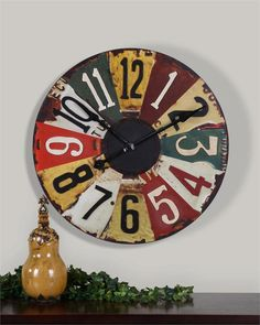 """Completely cool....license plate clock. Site says: """"This colorful clock face consists of vintage pictures of old license plates with rustic bronze details.  Quartz, battery operated movement Dimensions (inches): 29 W X 29 H X 2 D"""""""