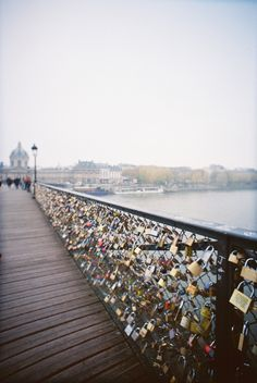 Love lock bridge in Paris. The idea is, couples or friends go to the bridge Passerelle des Arts in Paris from all around the world. They simply write their names on a padlock and attach it to the bridges railing and then throw away the key in the Seine river to symbolize their undying love.