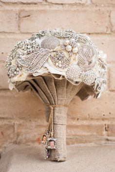 This broach bouquet was hand made by the bride's mother. What made it special was the four small charms with pictures of all of her grandparents that had passed. It was her way of including them in her wedding