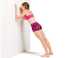 Tone Your Whole Bod With a Wall: Stand with feet hip-width apart, facing wall about 1 foot away, arms extended and hands on wall. Engage abs and bend elbows and lower torso toward wall (as shown). Return to start for 1 rep. Do 20 reps. Works arms, chest, abs #SelfMagazine