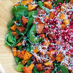 Spinach salad recipe with roasted cinnamon-maple sweet potatoes, bacon, pomegranate seeds & gruyere cheese. Easy Thanksgiving, fall winter side dish.