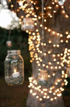Autumn tree with string lights and jar lanterns with candles...
