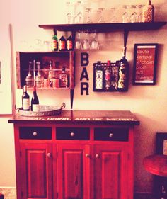 """DIY home bar using an old buffet, scrap wood shelving, magazine rack, old crate, DIY """"cheers"""" sign and ikea under mount wine glass carrier."""
