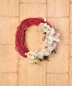Turn a rustic grapevine  wreath tropical with burnt red  spray paint and a cluster of  cymbidium orchids.