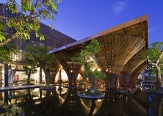 Fifteen conical bamboo columns support the roof of this waterside cafe.