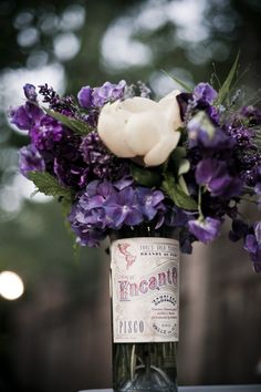 vintage pisco bottles used as centerpieces. so pretty mixed with those beautiful purple blooms  Photography by http://vieraphotographics.com, Floral Design by http://sharlaflockdesigns.com