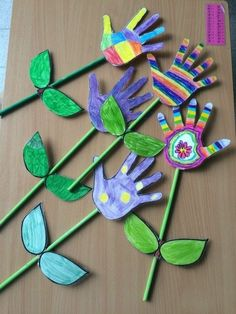 five flowers made from hand-painted hand-shaped cutouts, in different colors, with green straw stalks and paper leaves