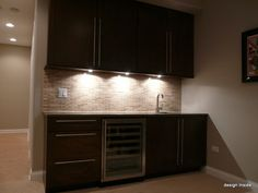 Completed wet bar with accent lights and wine fridge