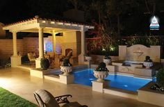Pool with Covered Patio - Deep-seating patio furniture and a custom fireplace bring the comfort of indoors right to the poolscape.  Photo courtesy of Pacific Paradise Pools http://www.luxurypools.com/