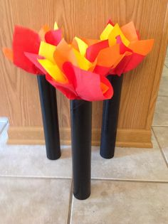 Torches for Kingdom Rock VBS. Cardboard poster tubes cut in half & spray painted black. Red, orange & yellow napkins for flame.  Attach to wall with command hooks & paper clips to slant away from wall.