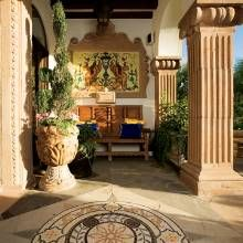To the right of the front door, a tile mural that was hand-painted in Guadalajara, Mexico, hangs above a wooden bench. Potted containers, a beamed ceiling, and a tiled floor medallion complete the welcoming space.