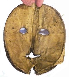 """1583 English: """"The inside is strengthened by a pressed-paper inner lining with 3 layers stitched together by a black cotton thread. On the silk lining, just below the centre of the mouth, is a loose thread of white cotton which would have held a black glass bead (found in association with the mask). With a lack of holes to allow string or elastic to be put around the head, the mask would have instead been held in place by the wearer holding the black bead in her mouth."""""""