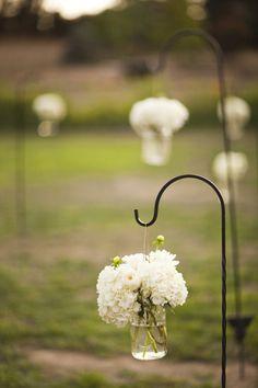 Beautiful idea for an outdoor wedding walkway hook, white flowers, yard, purple flowers, hanging flowers, flower decorations, aisle flowers, mason jars, outdoor weddings