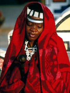 North of Pretoria, South Africa, Ndebele bride Zanelle stands wrapped in her marriage blanket, which she will wear at special events for the rest of her life. The Ndebele celebrate weddings in three stages, which can take years—the third stage is only completed with the birth of a child.