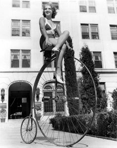 Grace Bradley braves an antique bicycle. June, 1933