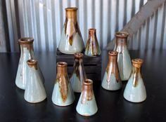 Bottle vases - Jon Loer 2013 - Remember high school science class ?  Slipcast beakers with blue celadon glaze and iron/rutile stain on the lips