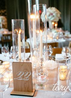 Such a chic table setting with candles, floating flowers and wood table number.