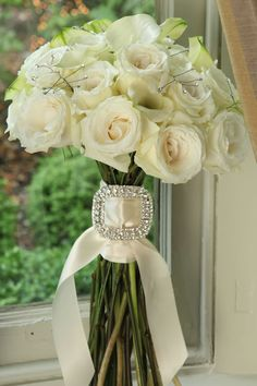 A rhinestone-encrusted buckle adds some sparkle to this bouquet of white roses and calla lilies.