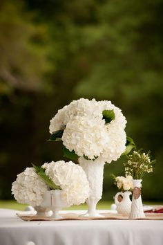 pretty all white centerpiece with milk glass and hydrangeas