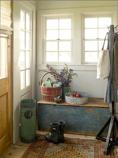 An antique trunk provides convenient and much needed storage just inside the front door of a compact home.