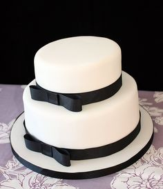 Black & White Wedding Cake -   Simple white 2 tier stacked wedding cake tied with black ribbon. Top tier is lemon and the bottom is chocolate sponge.