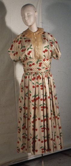Circa 1959 Cherry Printed Ivory Silk Surah and Organdy full skirted dress with wide cummerbund and short dolman sleeves. Front bodice open to cummerbund and filled with organdy dickey with peter pan collar.  Via Fine Arts Museums of San Francisco.