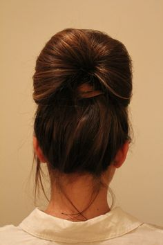 From underneath, find the approximate middle of the ponytail and put your fingers through to the other end rab the end of the ponytail and pull it through the hole. Pull about 2-3 inches of hair through, tighten pony, and secure ends.