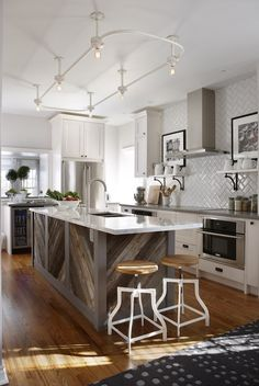 LOVE the wood on the island---Stunning kitchen with gray paint color, Ikea kitchen cabinets with Silestone Grey Expo countertops, barnboard kitchen island with calcutta marble countertop, herringbone tile backsplash, white shelves flanking induction cooktop, white swivel stools from Morba, glass-front wine cooler and vintage shower enclosure lighting.