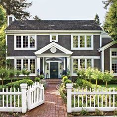dark shingle house with white picket fence