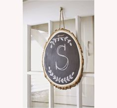 Check out this easy DIY wreath alternative--a hanging monogrammed chalkboard wood slice with instructions from Caitlin Swann at mydailybubble.com