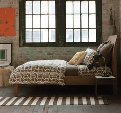Exposed brick bedroom. Love the industrial warehouse feel paired with the warmer earth tones.